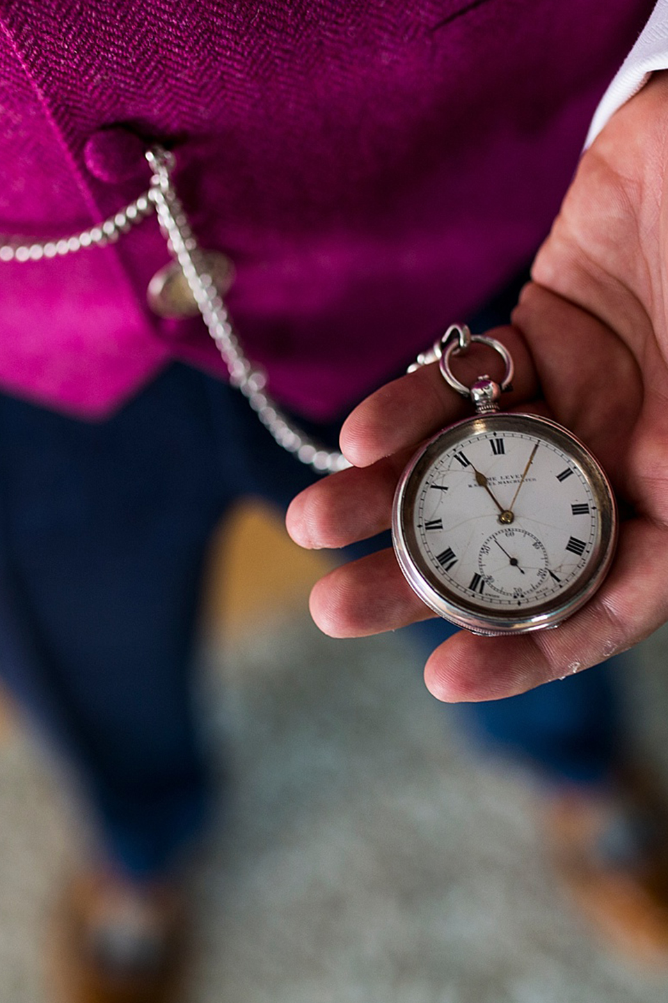 A close up of the groom's pocket watch tied to his purple waistcoat – wedding ideas