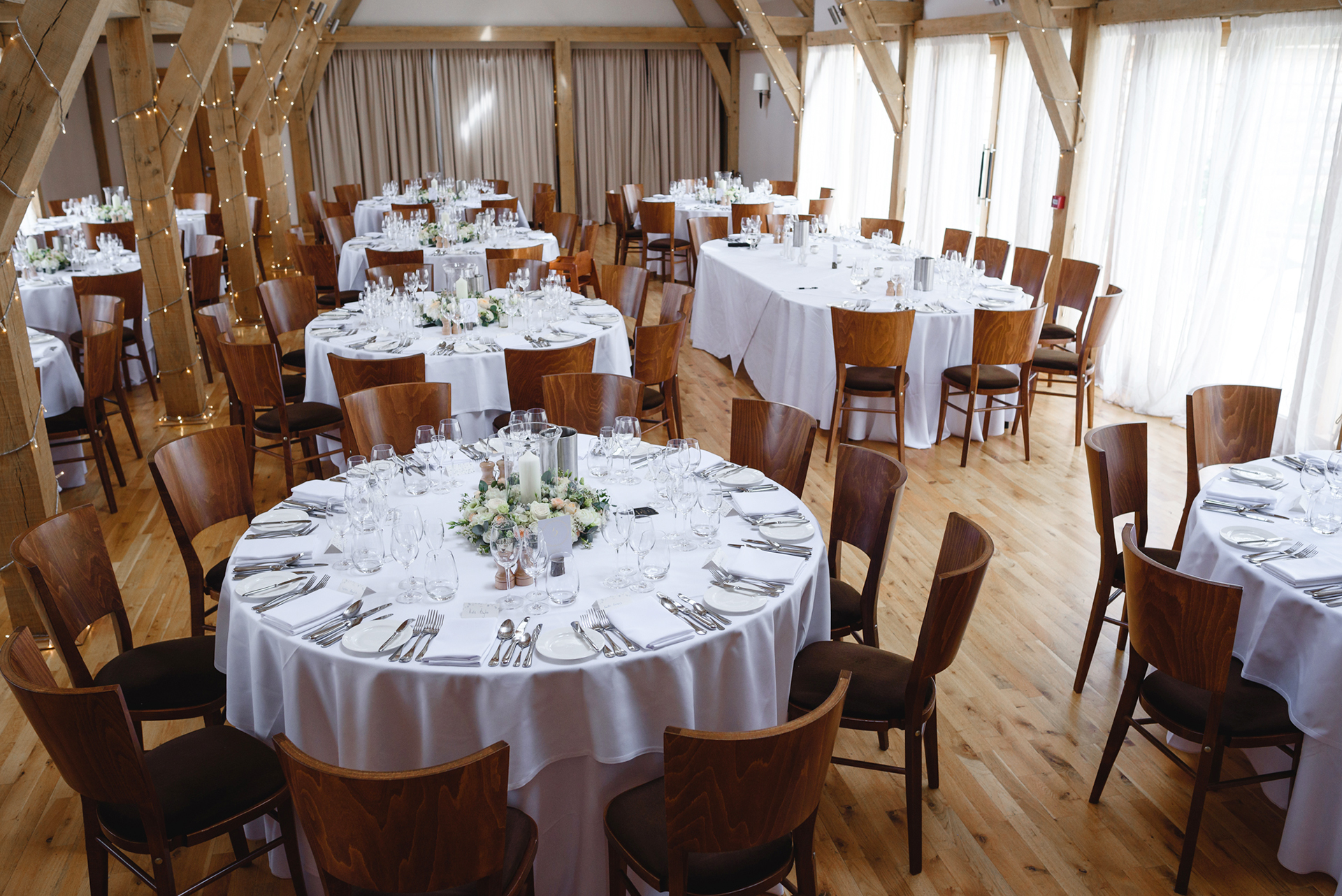 The beautiful wedding barn set up for the wedding breakfast with candles in hurricane vases on each table