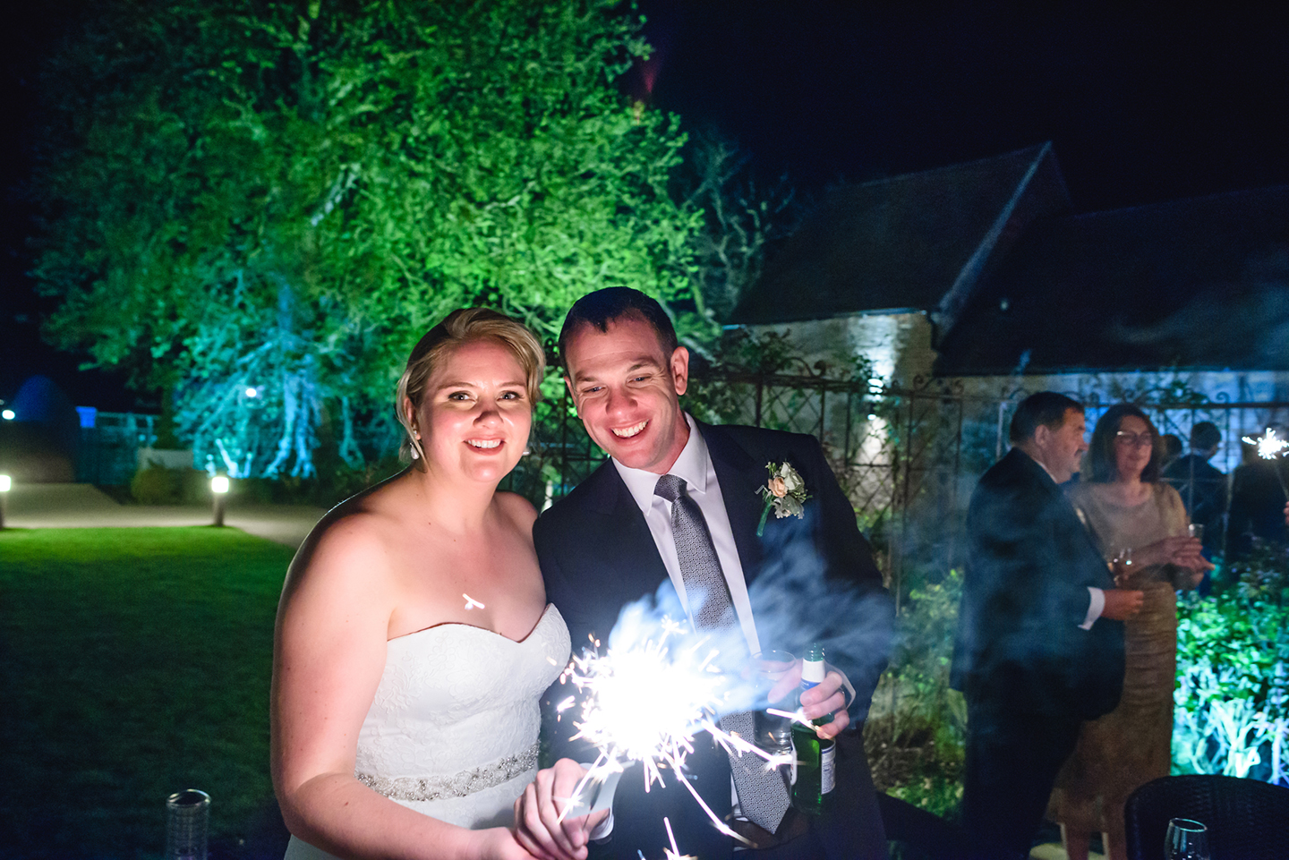 The bride and groom enjoy lighting sparklers during the evening reception at this beautiful Cambridgeshire wedding venue