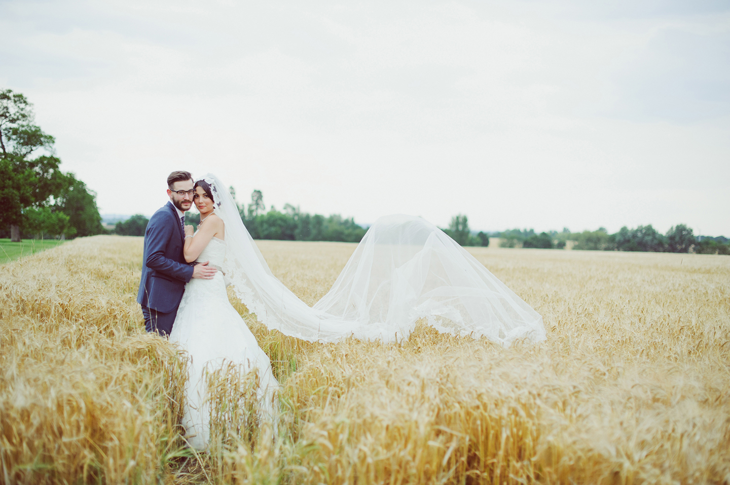 A bride and groom make use of the Cambridgeshire countryside that surrounds this barn wedding venue