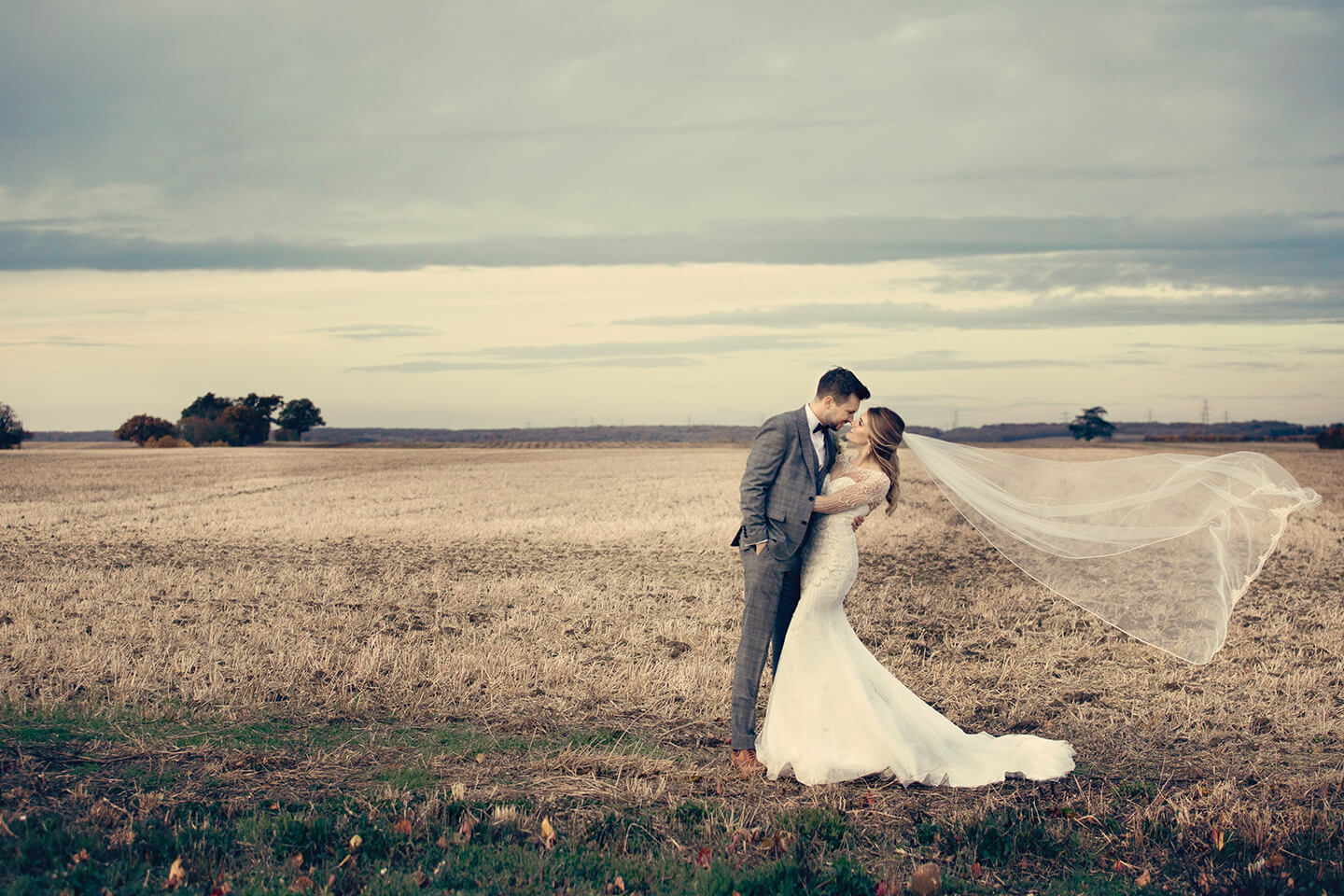The bride and groom steal a moment in the countryside surrounding of this stunning Cambridgeshire wedding venue