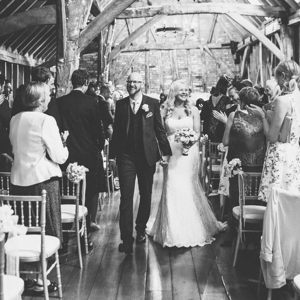 In the Rickety Barn at Bassmead Manor Barns in Cambridgeshire a bride and groom celebrate after saying their wedding vows