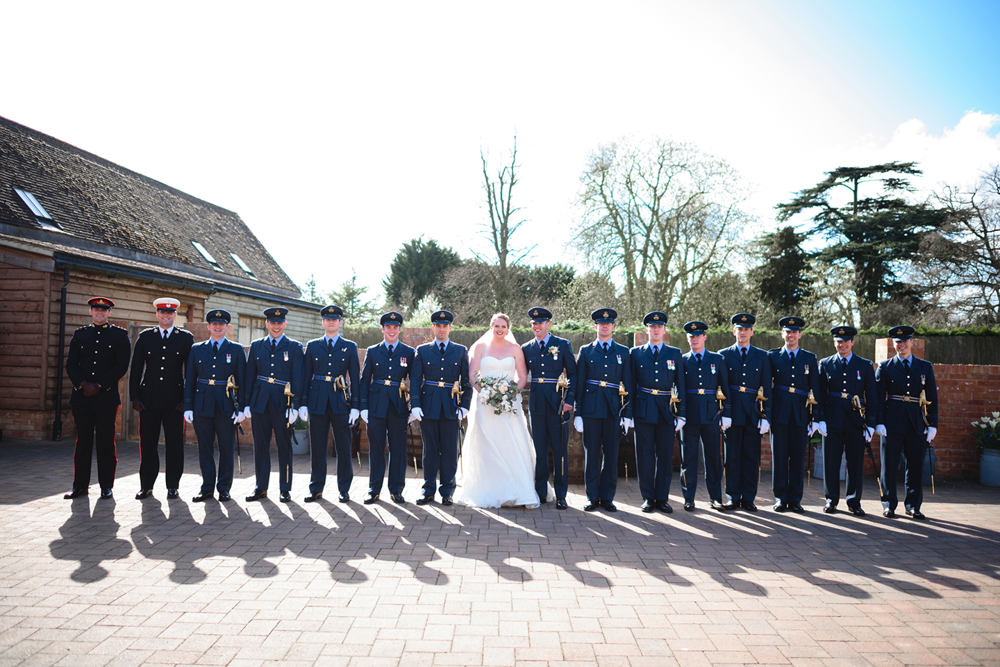 The bride stands with the groom and his groomsmen all wearing military suits to create a stunning wedding photo