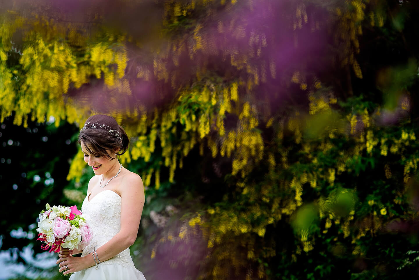 Bride stands in the grounds holding a wedding bouquet of pink flowers – wedding ideas