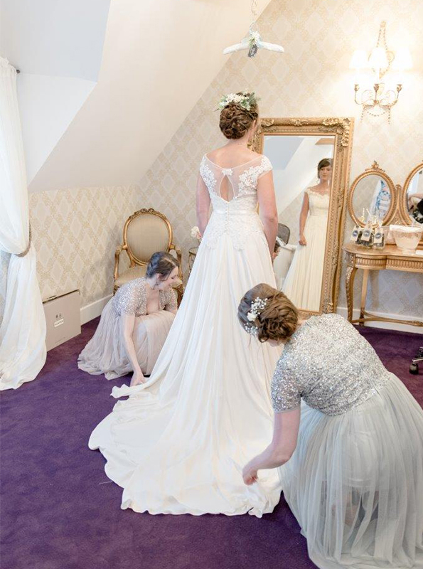 The bride gets ready in the Boudoir wearing her beautiful wedding dress as her bridesmaids help