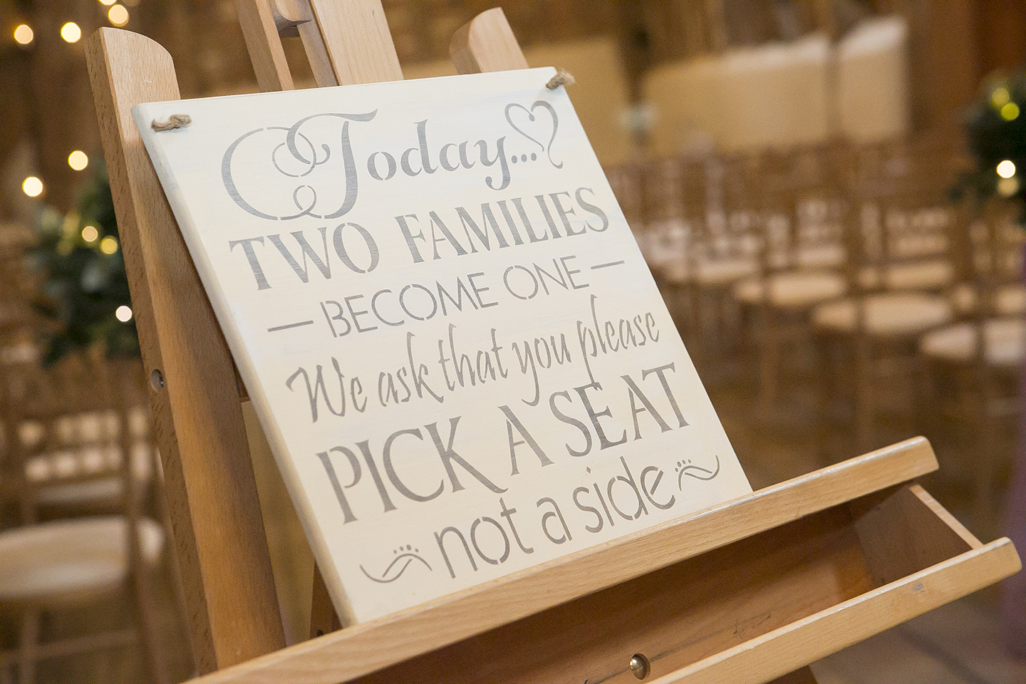 The bride used a wedding sign to encourage the two families to sit together during the wedding ceremony