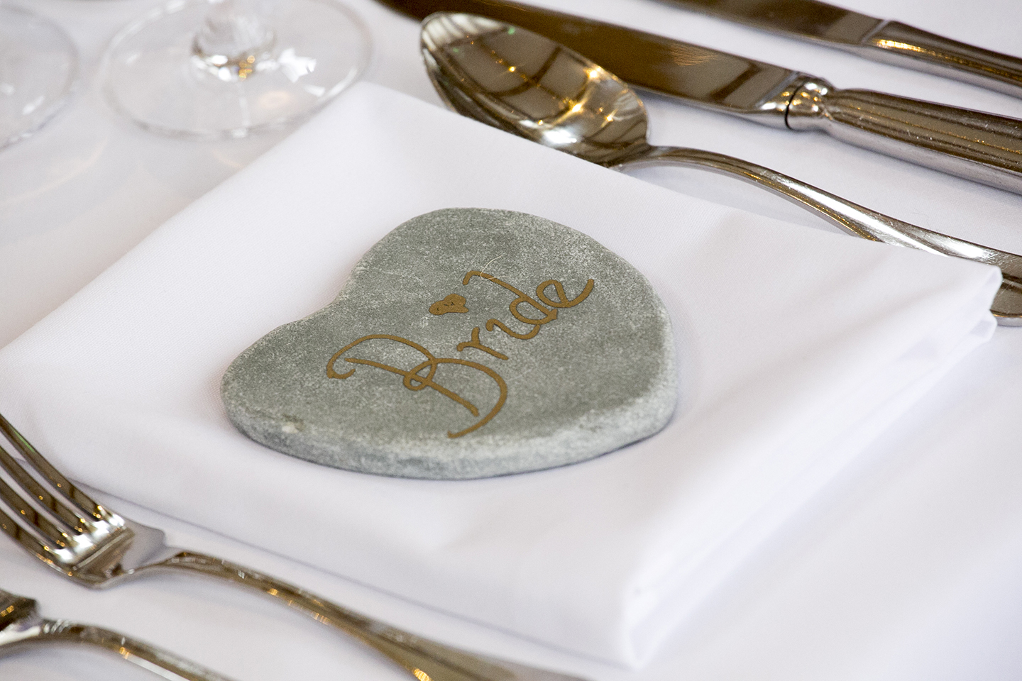 The couple wrote their guests names on heart shaped stones to create DIY table place names – wedding ideas