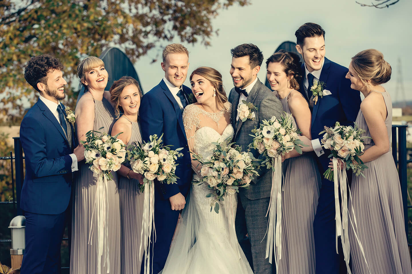 The happy newlyweds pose with their bridesmaids and groomsmen – grey bridesmaid dresses