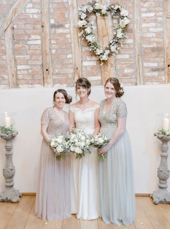 The bride and her two bridesmaids stand together in the wedding ceremony barn – grey bridesmaid dresses