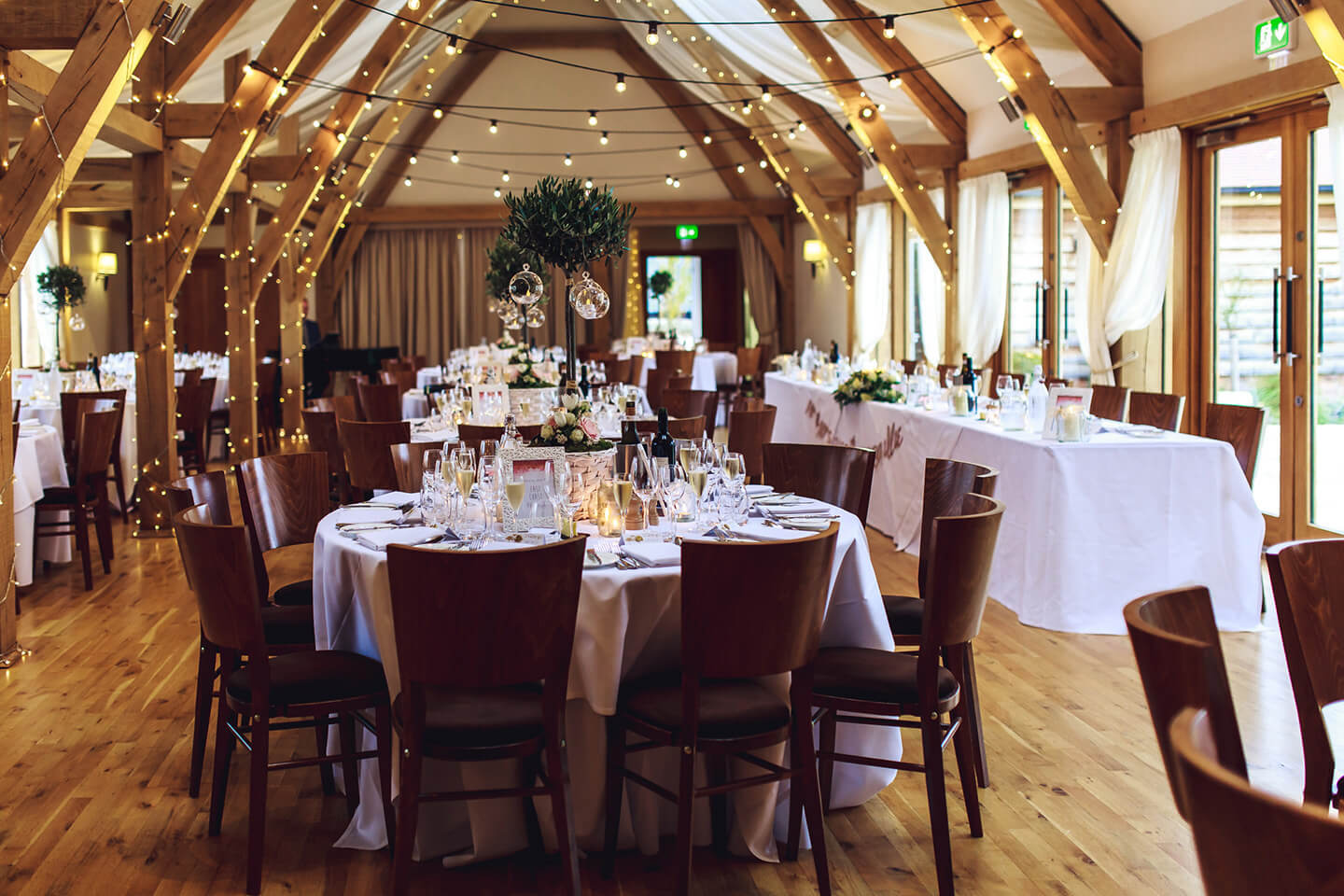The Bridge Barn is dressed for an autumn wedding breakfast with fairylights and greenery