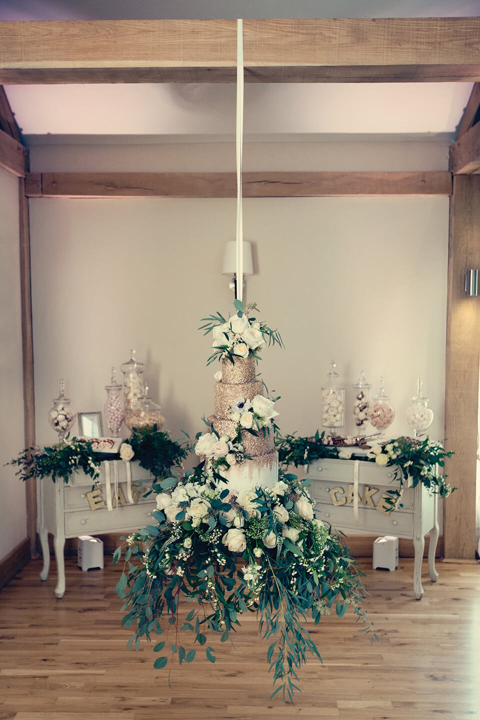 Guests were wowed by the couple's chandelier wedding cake decorated with white flowers and foliage and gold glitter