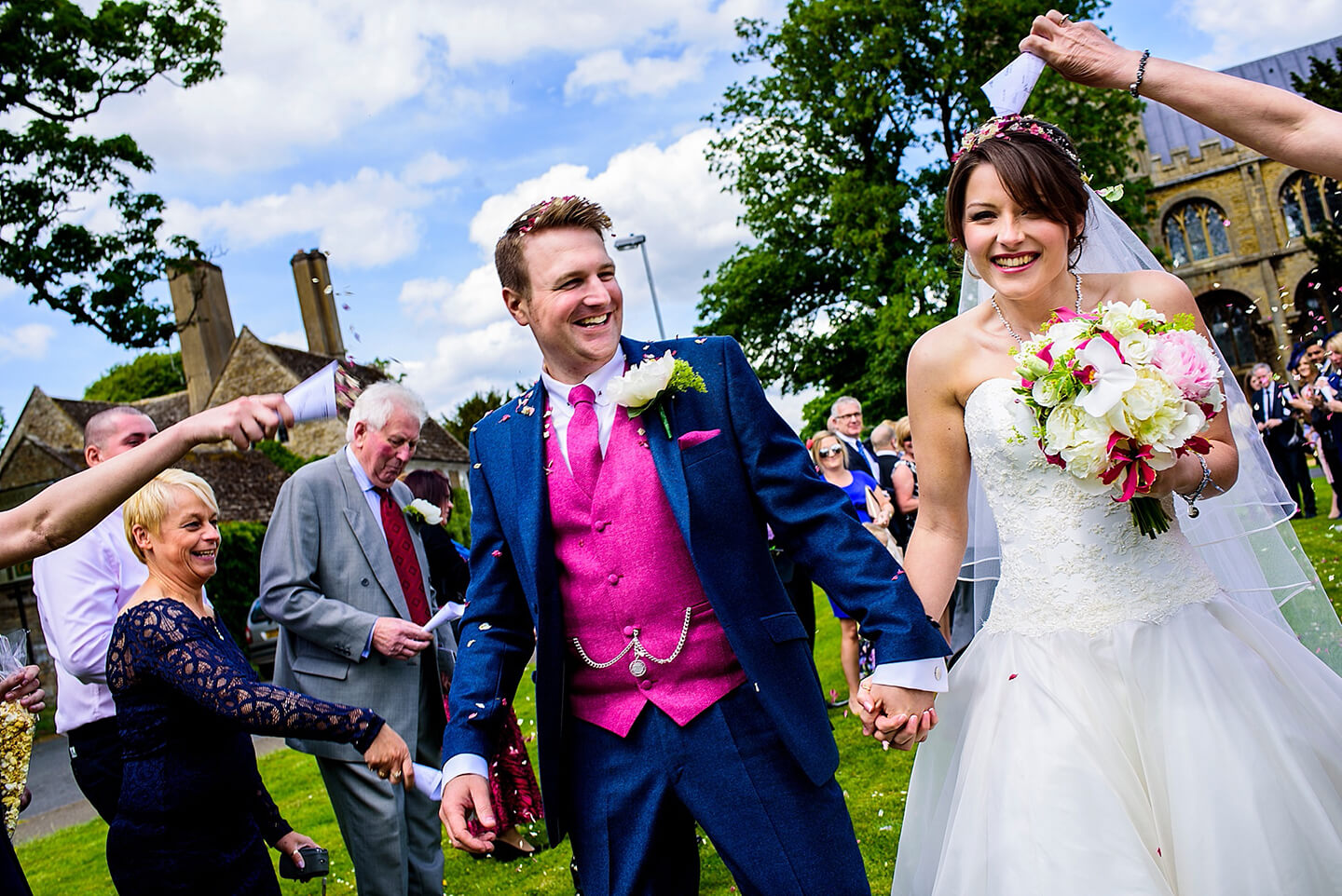 Guests throw wedding confetti as the happy newlyweds leave the church