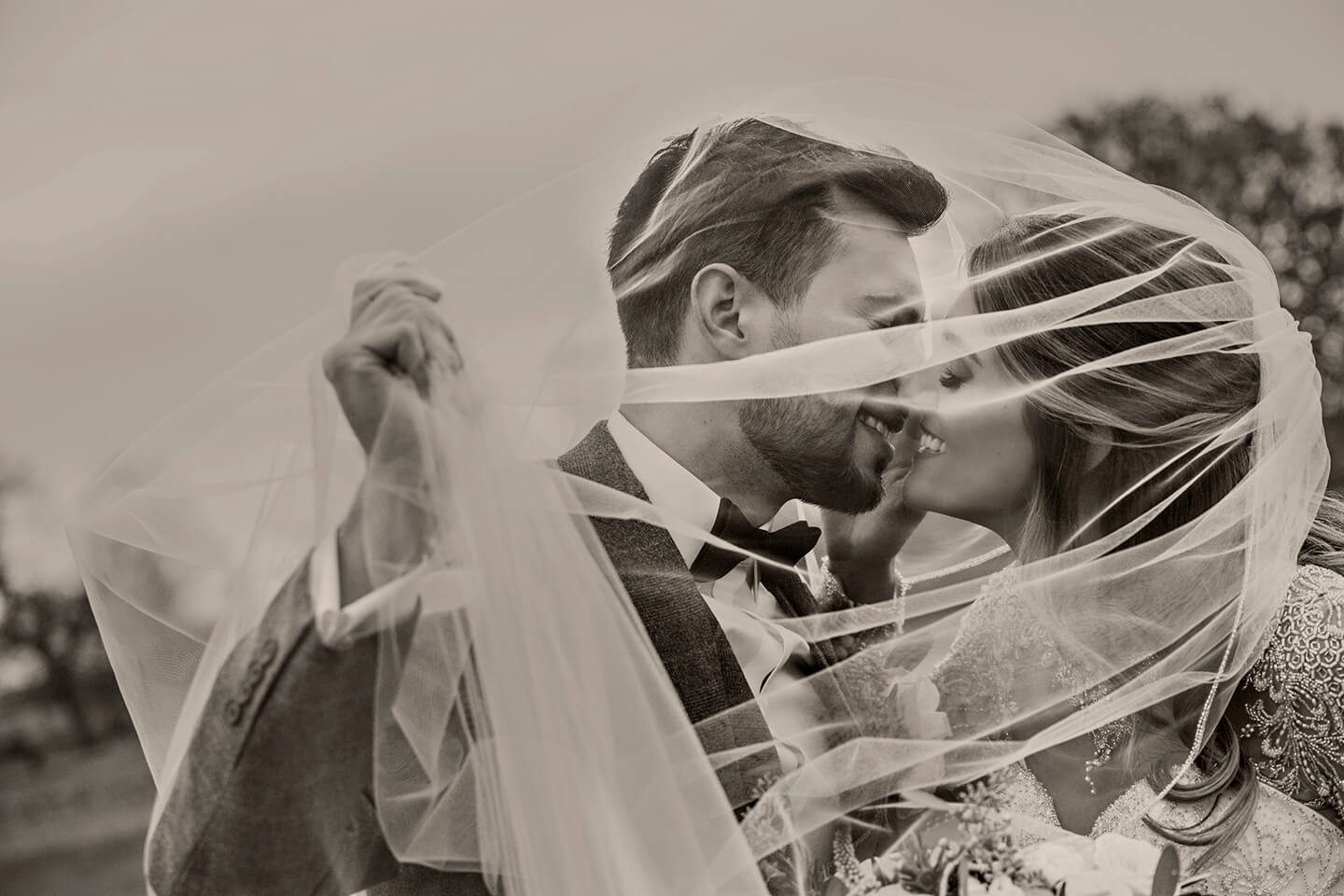 The happy couple kiss under the bride's wedding veil at this stunning country wedding venue in Cambridgeshire