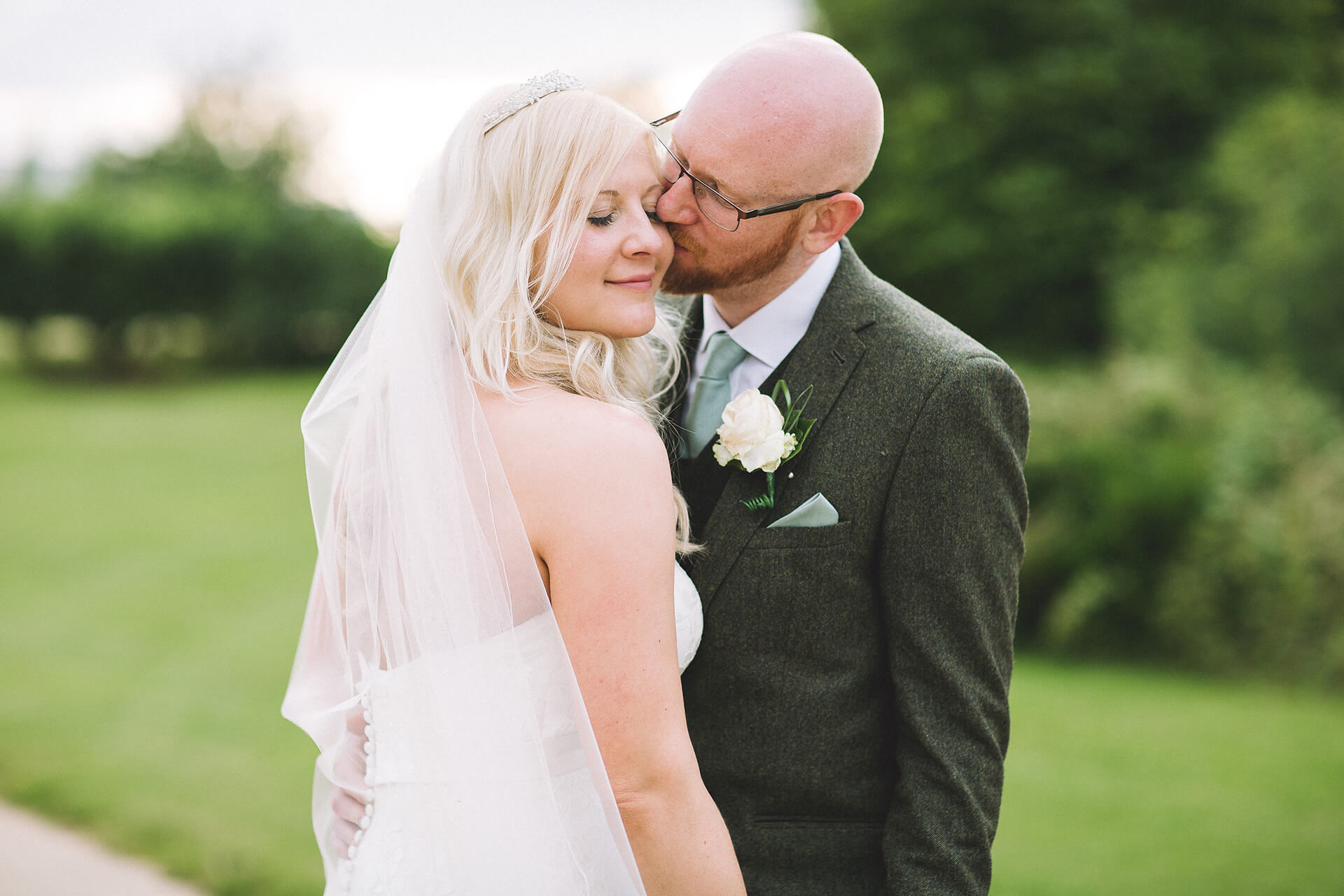 The groom kisses his bride in the grounds of this beautiful countryside wedding venue in Cambridgeshire