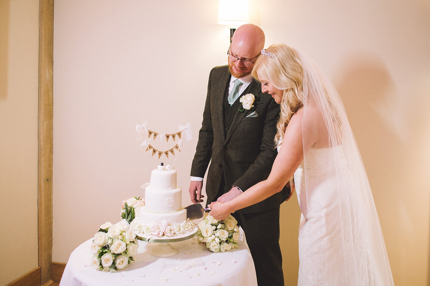 The happy couple cut their wedding cake together in front of family and friends – key wedding moments