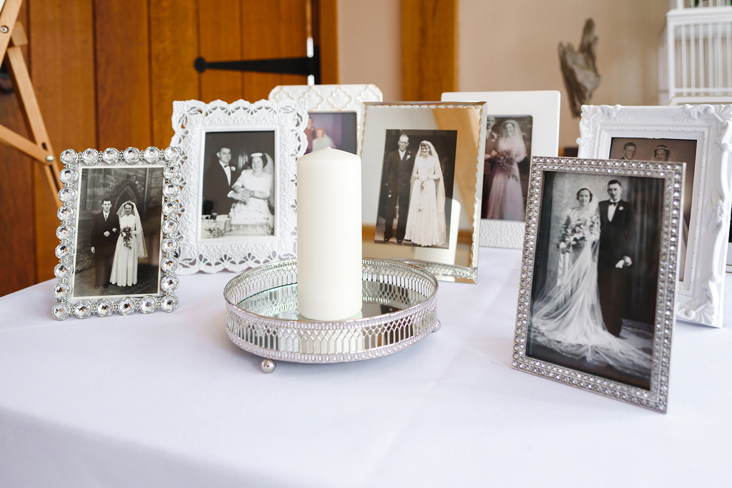 Family photos in white frames were placed on a table in the wedding venue to create a personal touch