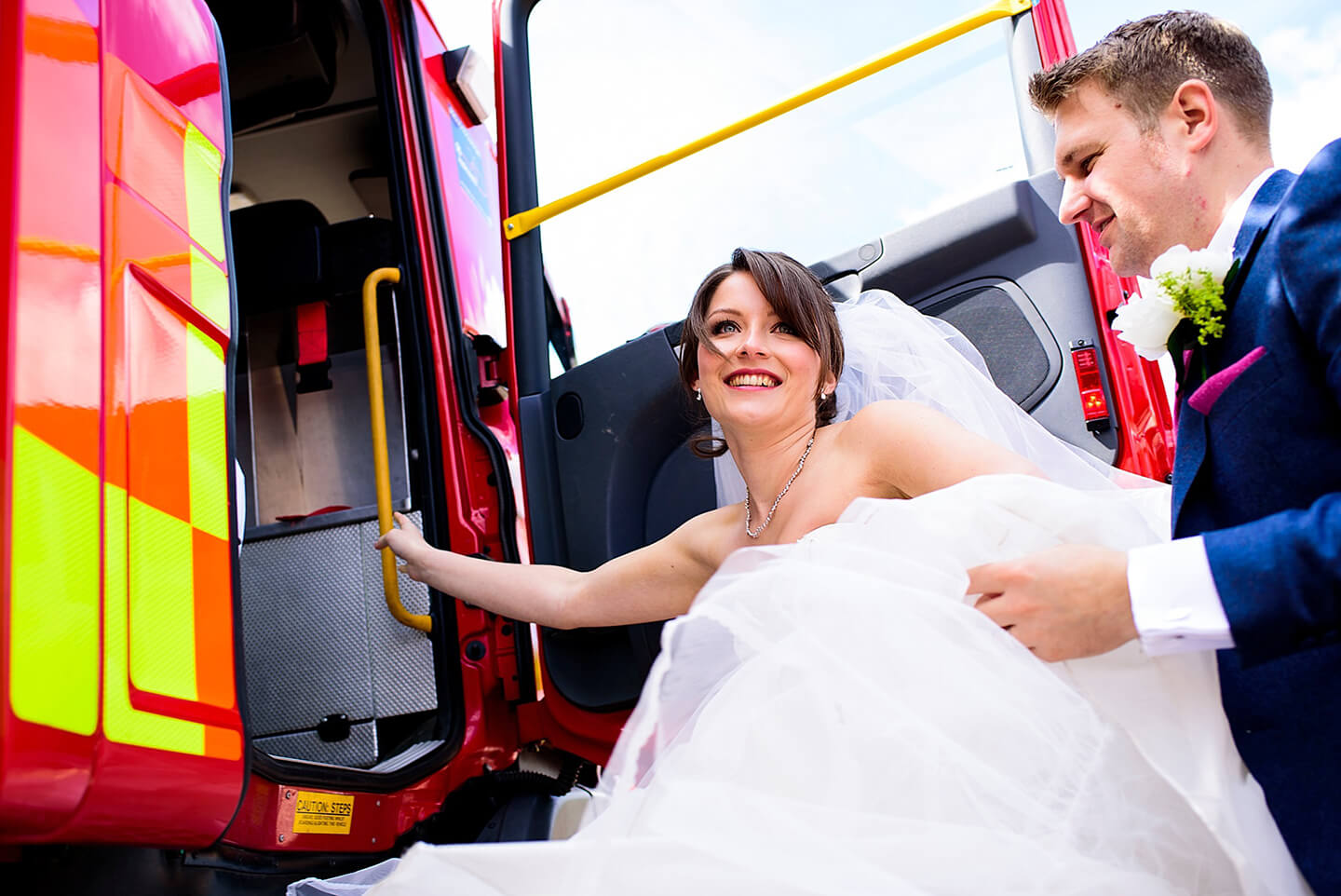 The bride and groom step into a fire engine as one of their modes of wedding transport – quirky wedding ideas