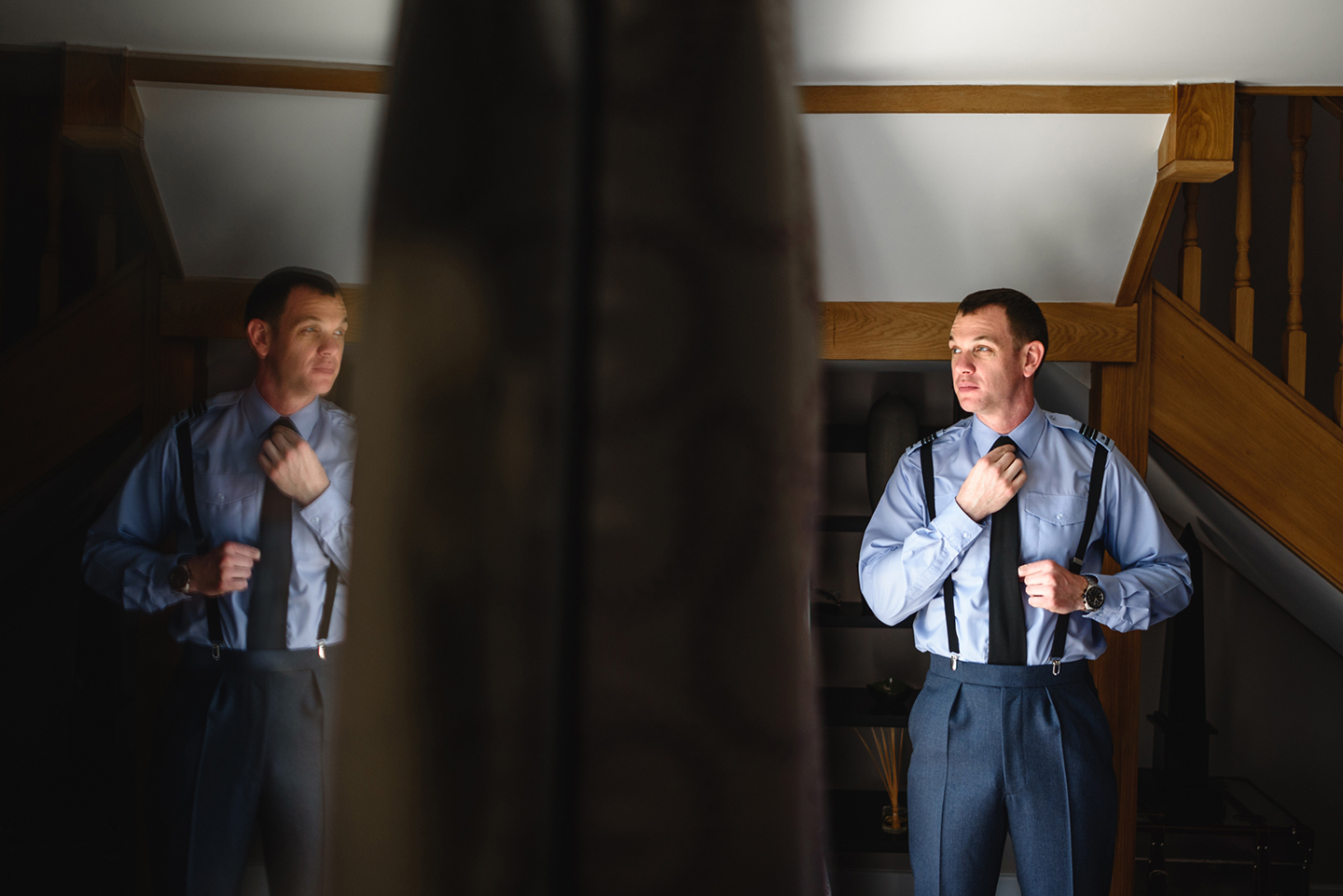 The groom gets ready for the big day ahead wearing his navy blue military suit