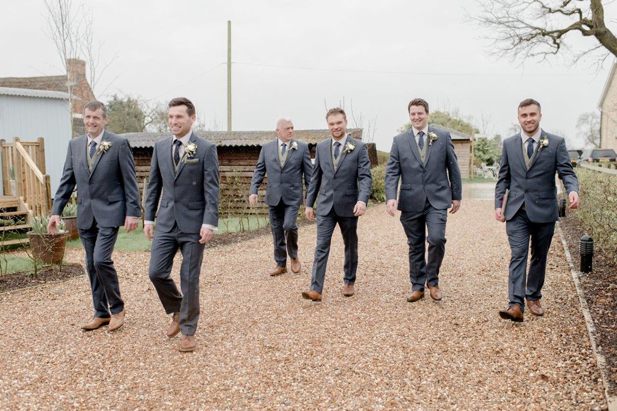 The groom and his groomsmen walk around the pretty country wedding venue wearing matching grey suits