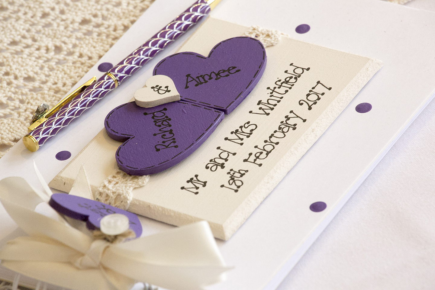 A purple and cream wedding guest book matches the theme for the day
