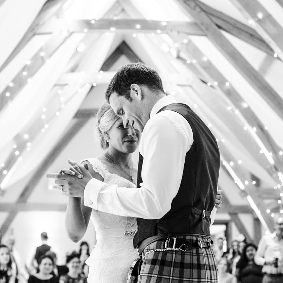 A new husband and wife enjoy their first dance in the Bridge Barn at Bassmead Manor Barns