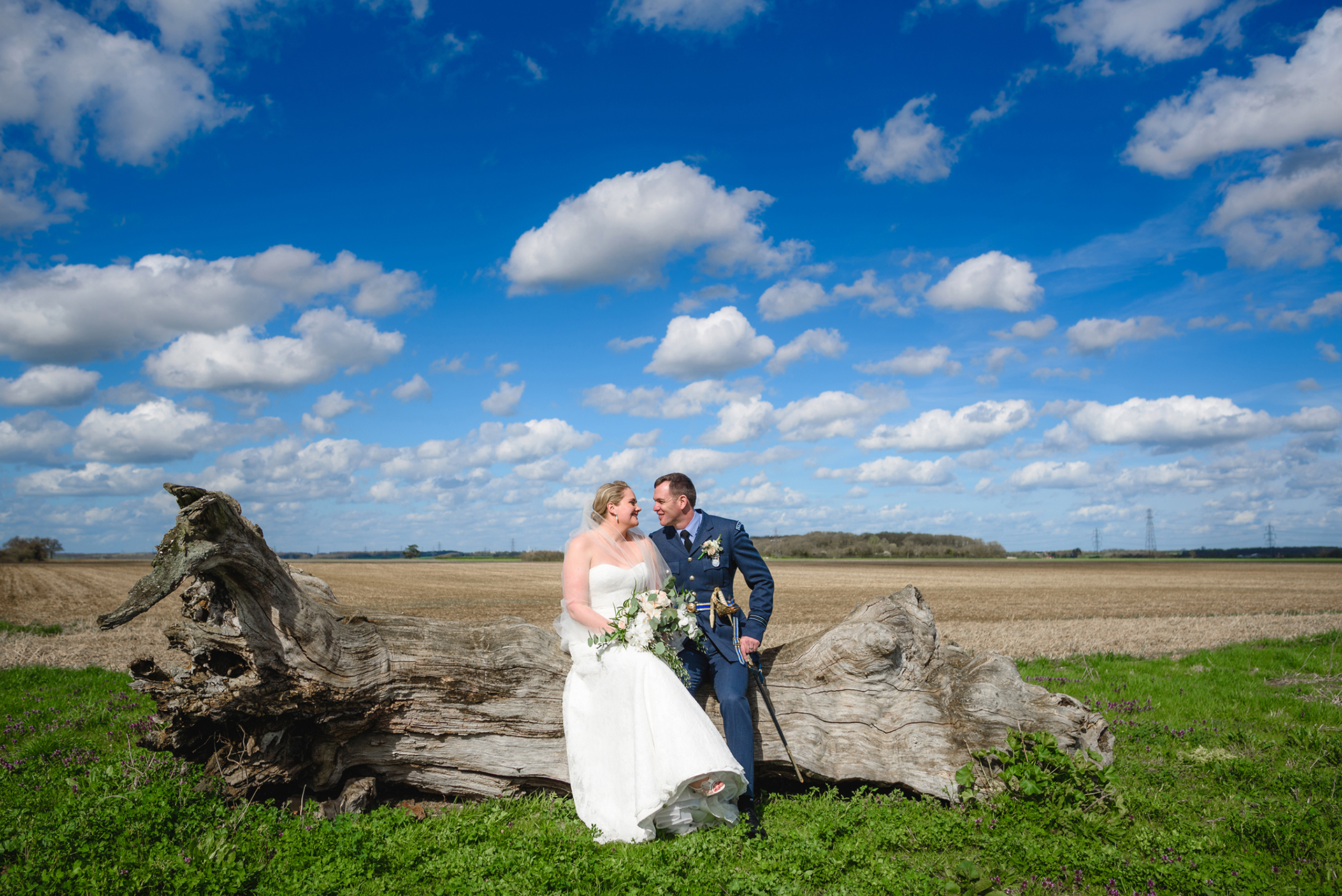 Laura and Nick take a moment out of their wedding day to sit on a tree stump and enjoy the countryside surroundings