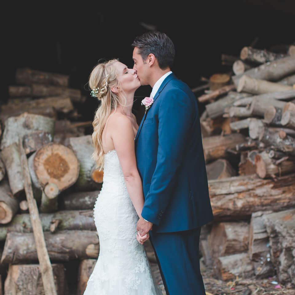 Newlyweds share a kiss in front of a beautiful log store at Bassmead Manor Barns wedding venue in Cambridgeshire