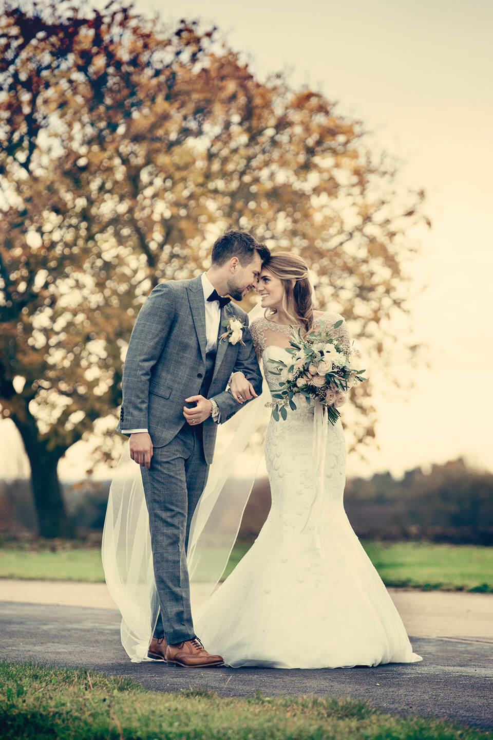 Nicola and Daniel walk arm in arm down the long drive leading up to the venue – wedding venues Cambridgeshire