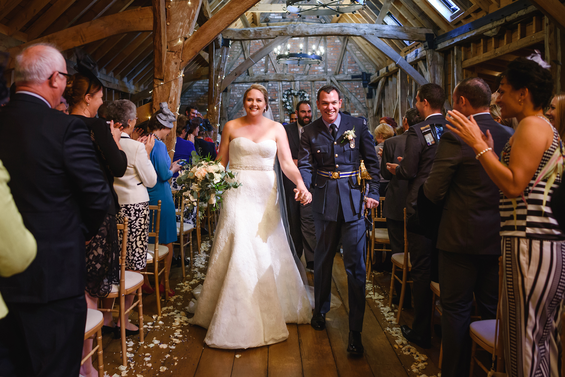 The newlyweds celebrate after saying their wedding vows in the Rickety Barn at Bassmead Manor Barns