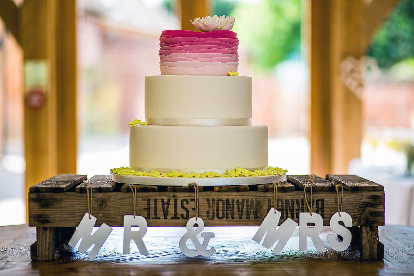 The couple had a three tier wedding cake with the top tier being ombre pink