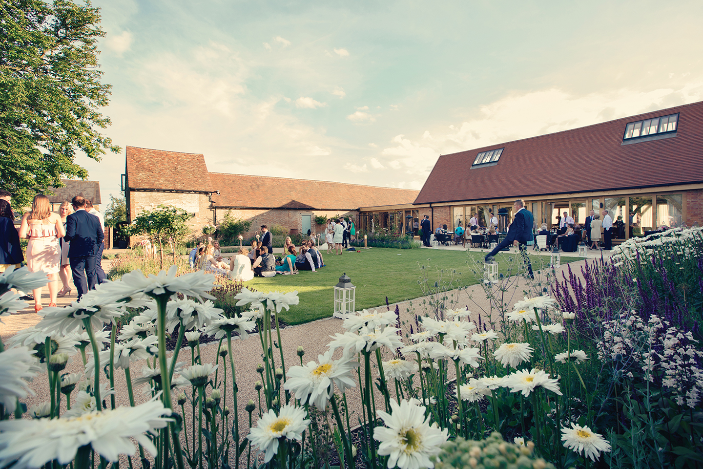 Guests enjoy an outdoor drinks reception in the gardens at Bassmead Manor Barns