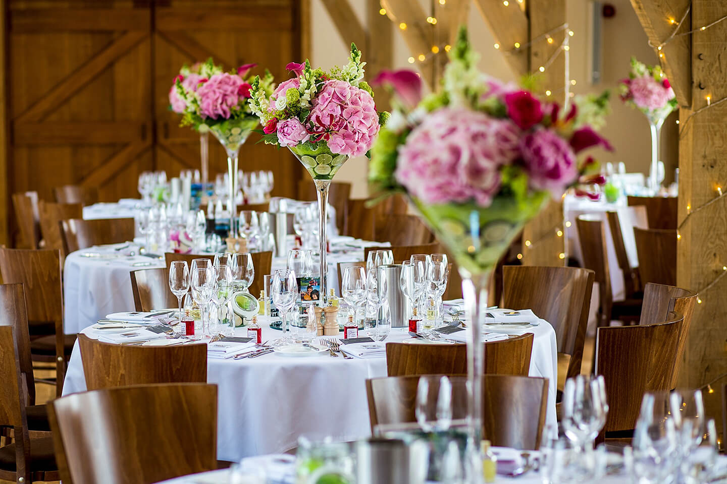 Tall vases filled with bright pink and green flowers make stunning wedding centrepieces