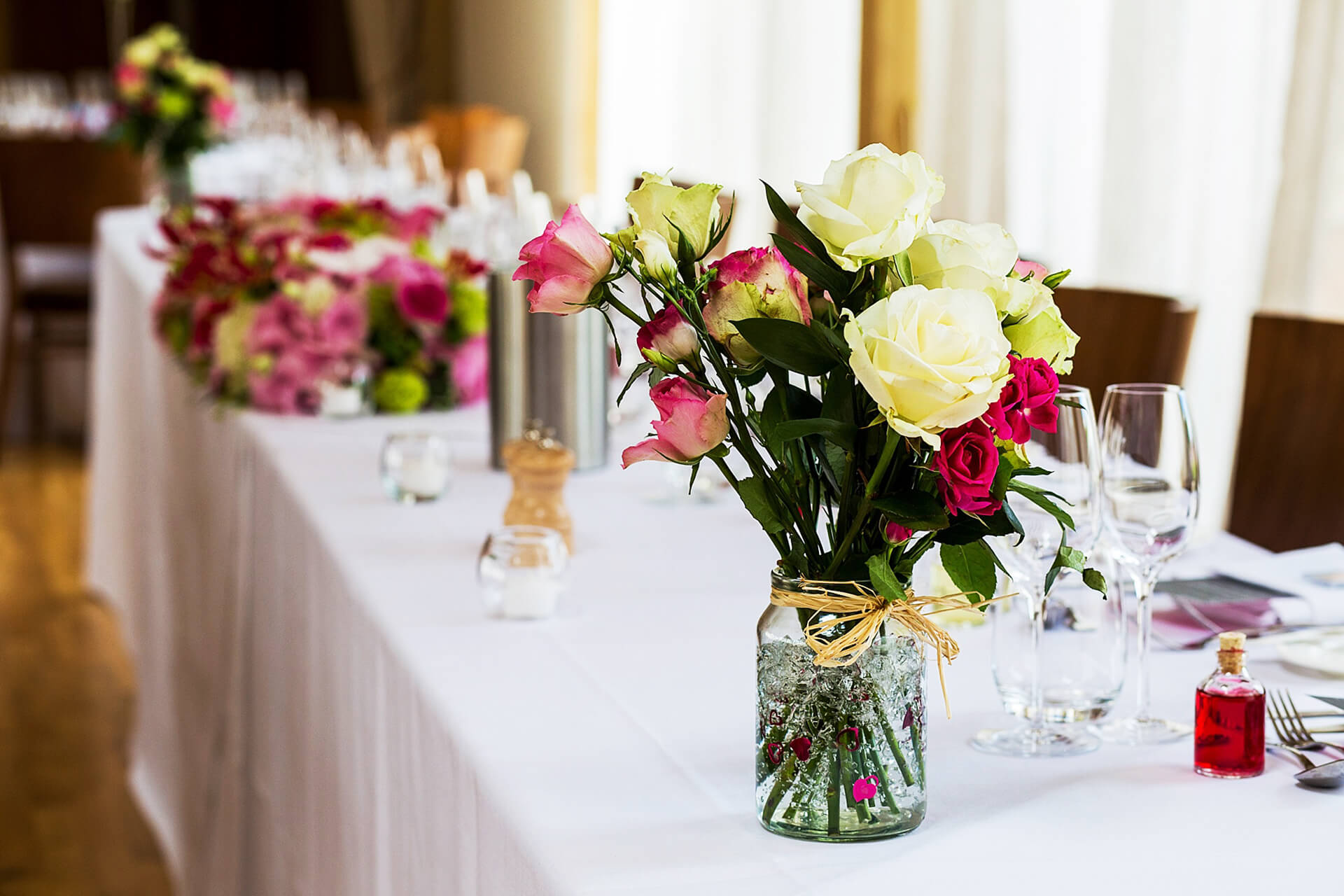 The couple decorated the top table with vases of pink and white flowers – wedding ideas