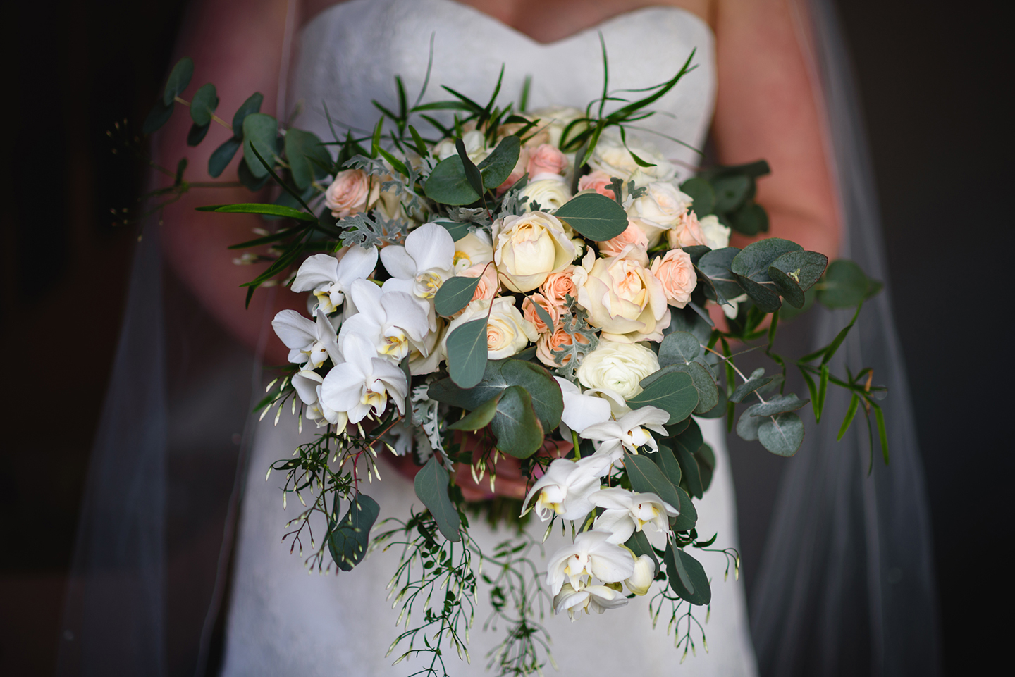 The bride holds her wedding bouquet featuring white flowers and green foliage – wedding ideas