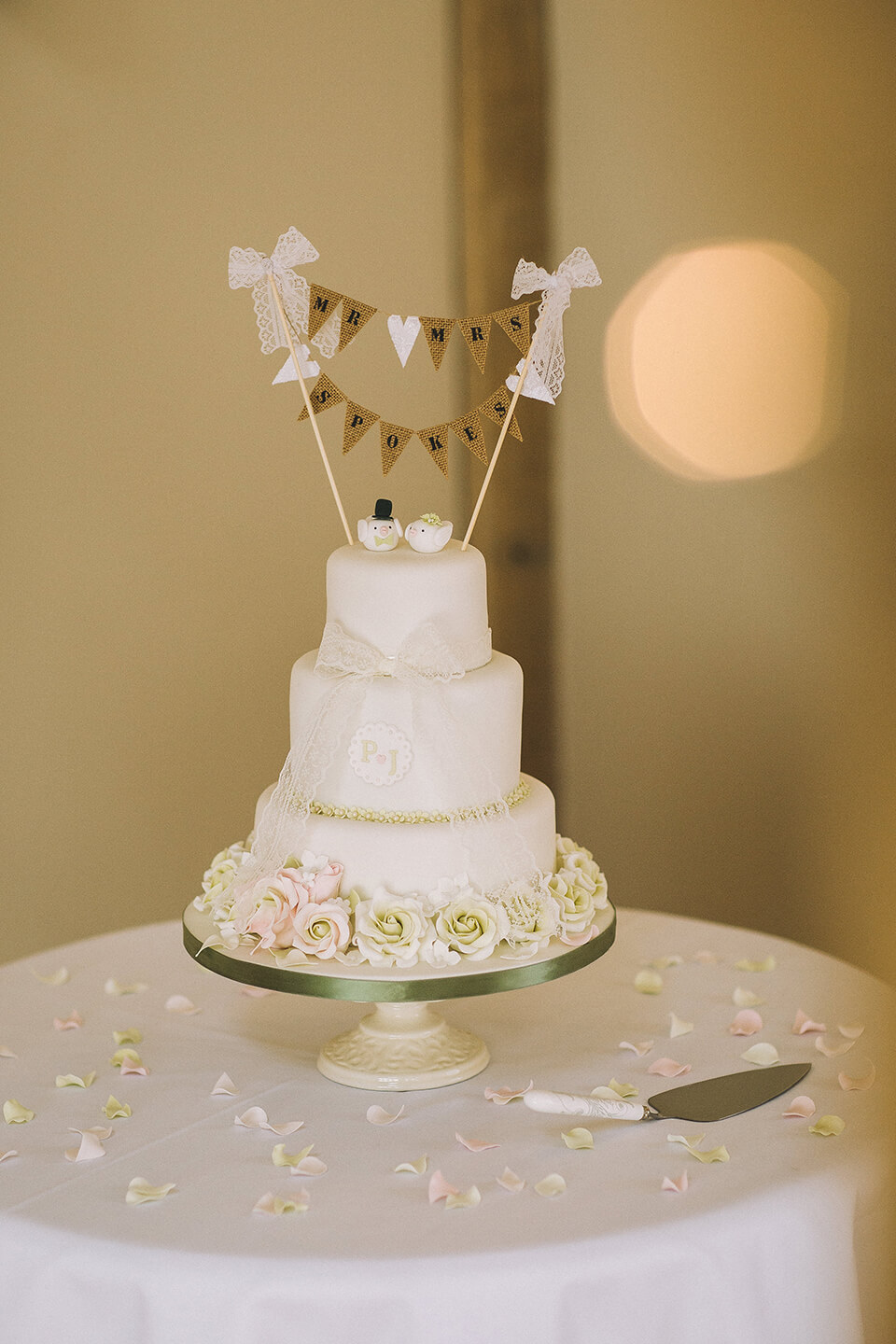 The couple had a three-tier wedding cake decorated with white roses and a bunting cake topper
