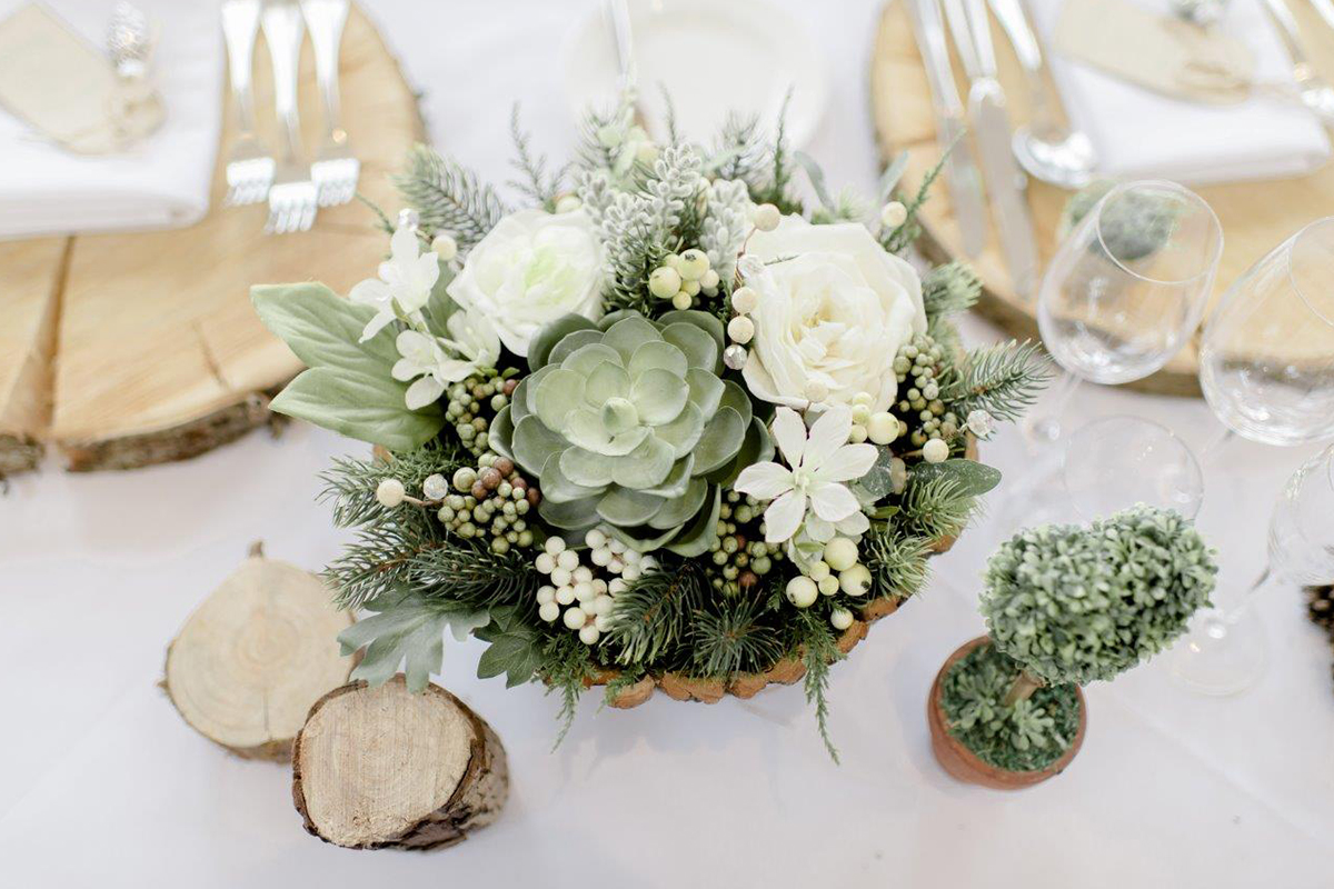 A close up of the wedding table centrepieces – white flowers and succulents