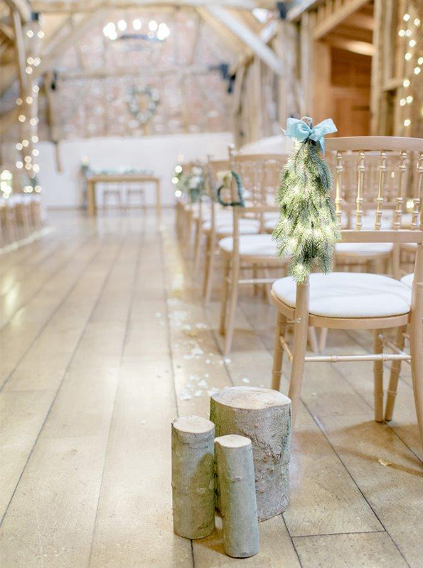 Bunches of sprigs tied with blue ribbon and rustic logs decorated the ceremony barn suiting the rustic wedding theme