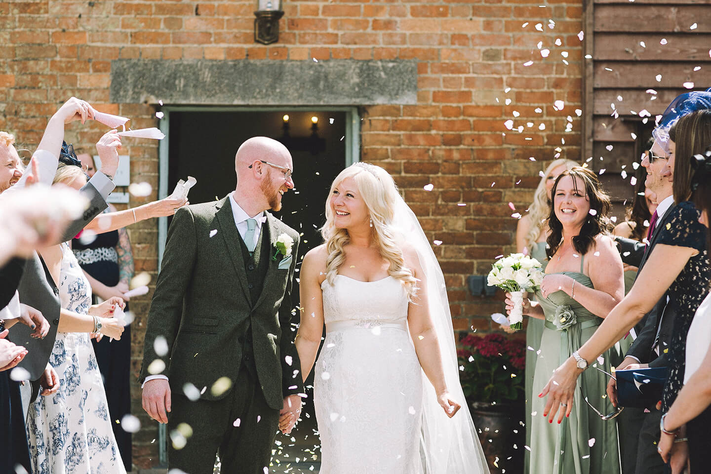 Guests congratulate the couple with wedding confetti as they leave the wedding ceremony