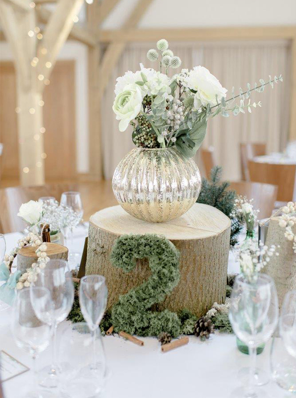A speckled vase contains white flowers and green stems and stands upon a tree stump – rustic wedding ideas