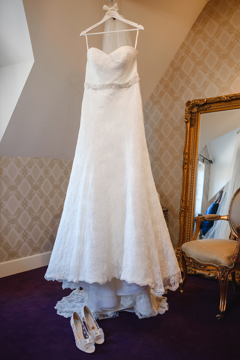 The bride's wedding dress hangs from the beams in the Bridal Boudoir