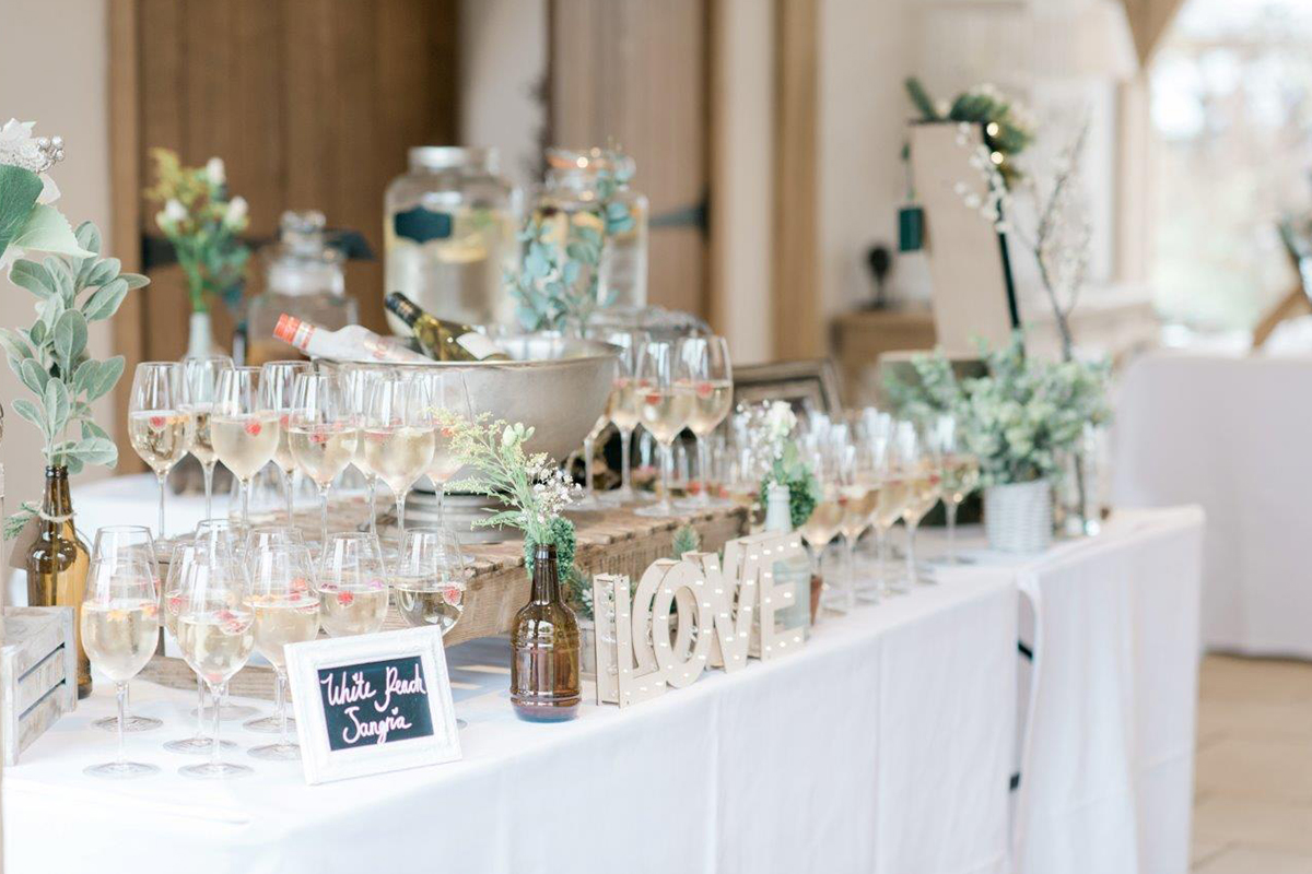 A table is set up with wedding reception drinks including champagne and other wedding drinks