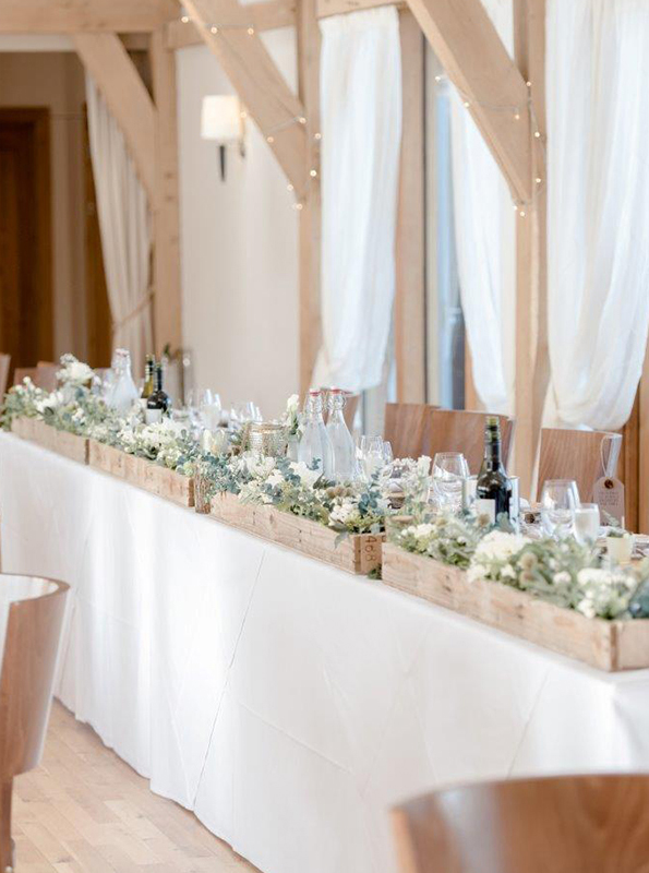 Wedding flowers sit in wooden crates to decorate the top table – wedding ideas