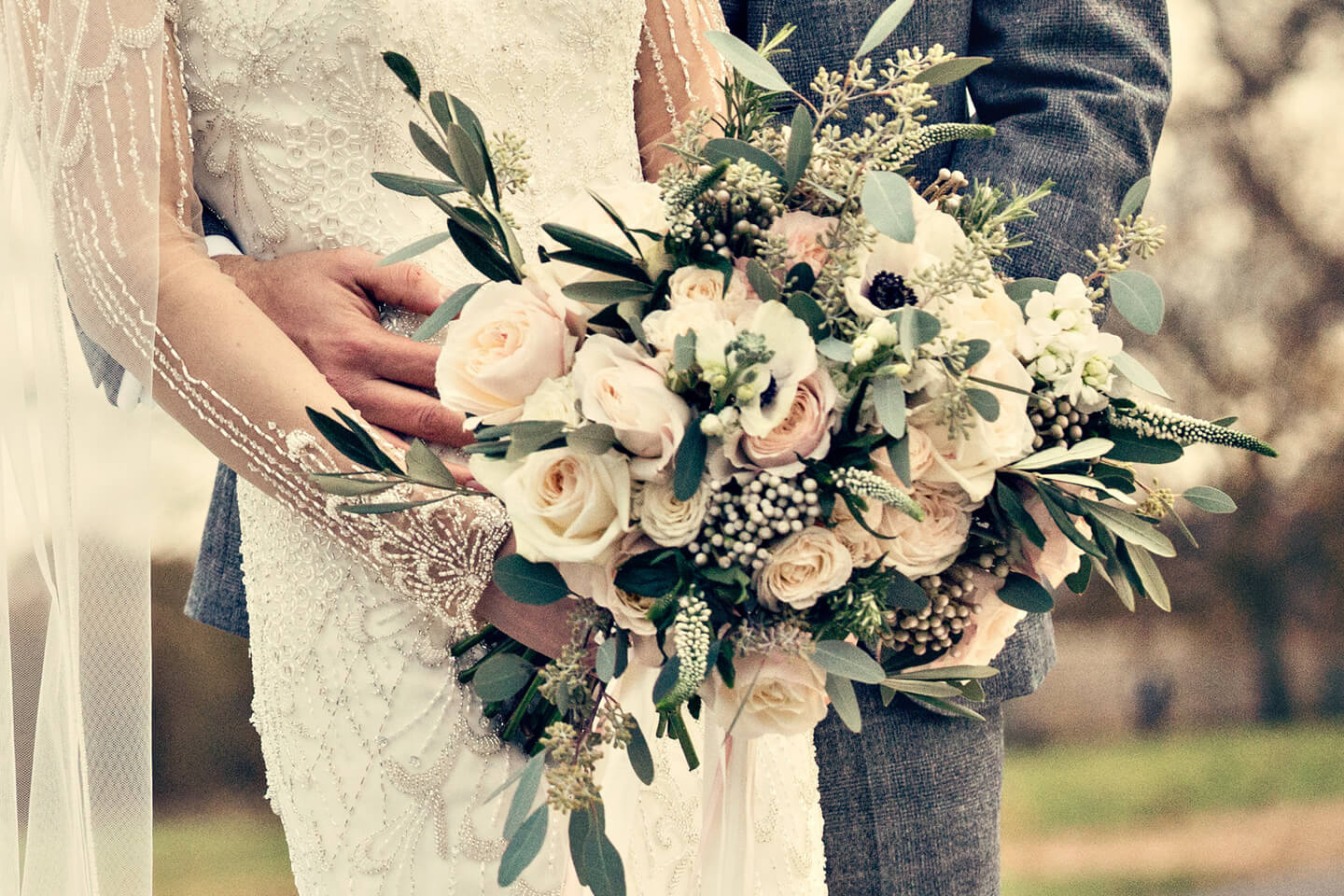 The bride holds her stunning winter wedding bouquet – a mix of blush pink and white roses with foliage