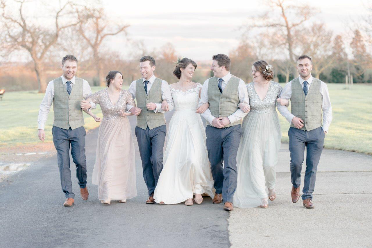 The bride and groom walk along the driveway with their bridesmaids and groomsmen