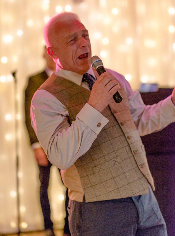 The groom's father sings the couples first dance song at their evening wedding reception