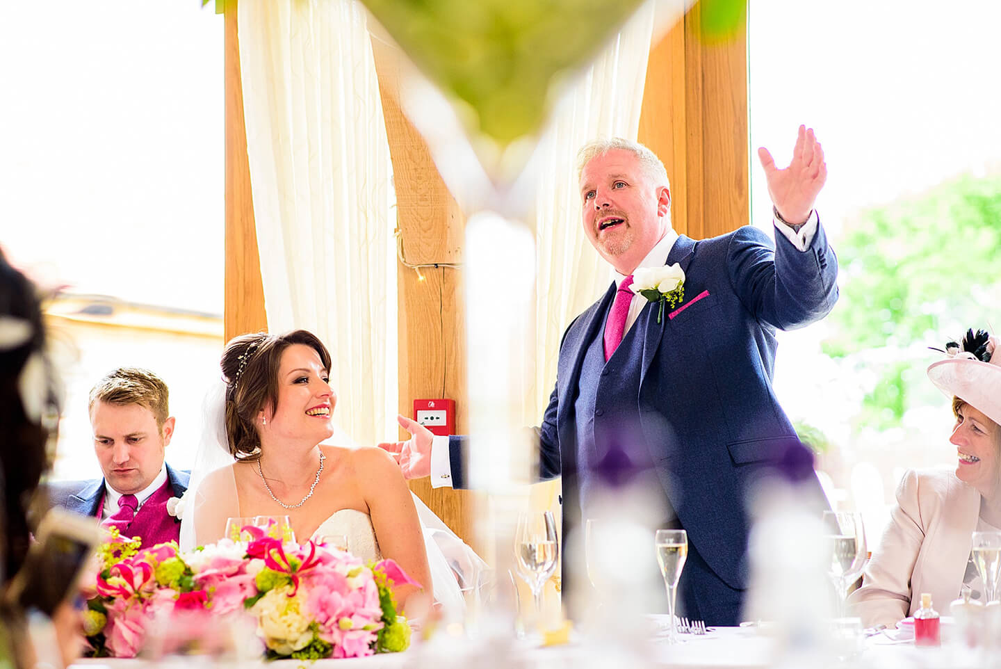 The father of the bride stands to begin the wedding speeches in the stunning Bridge Barn