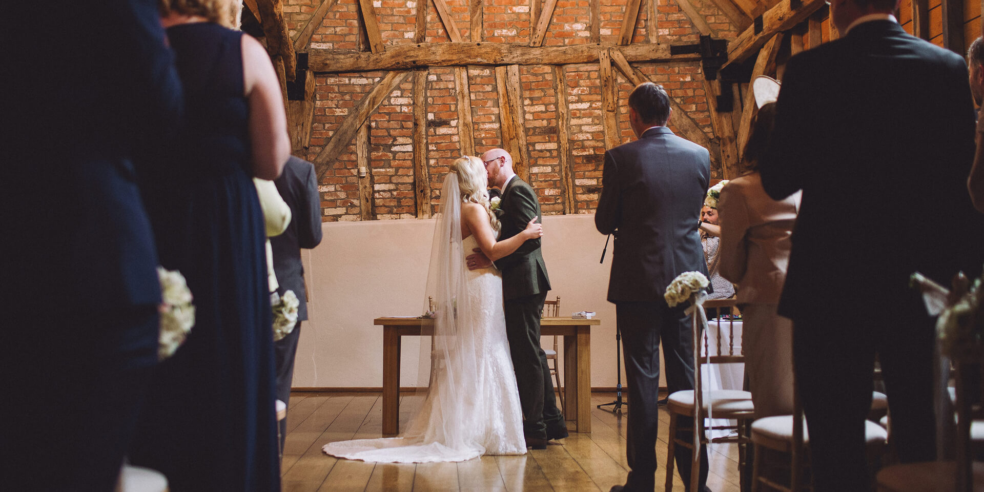 The couple seal their wedding vows with a kiss during their wedding ceremony inside the Rickety Barn