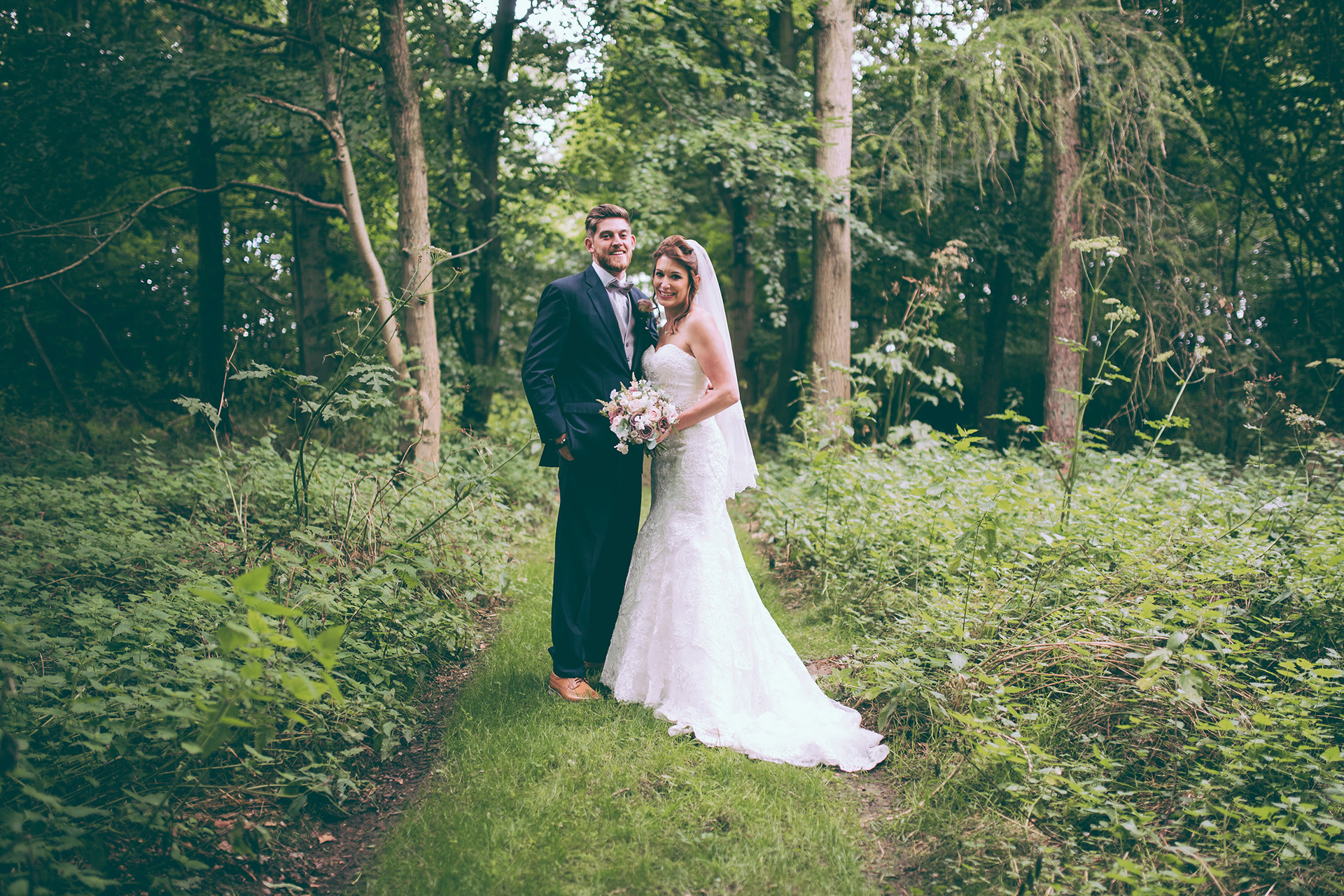The bride and groom make the most of the woodlands at Bassmead Manor Barns on their wedding day