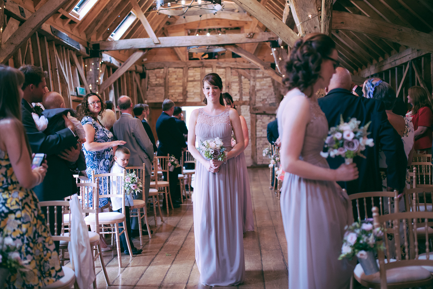Bridesmaids wore rose coloured full length dresses for this summer wedding at Bassmead Manor Barns