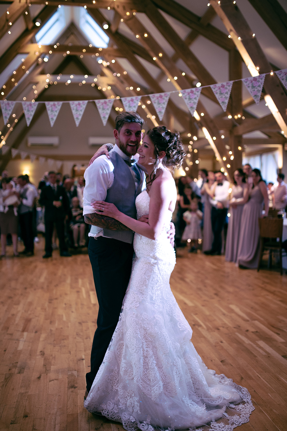 The bride and groom perform their first dance in front of guests at Bassmead Manor Barns